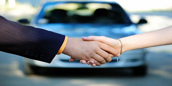 Photo of handshake in front of a car